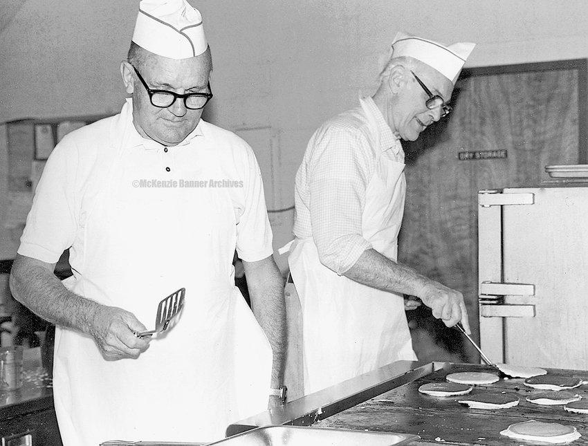 Bill Brush and Les Haugen flip pancakes at the Rotary Club Pancake Breakfast, 1982.