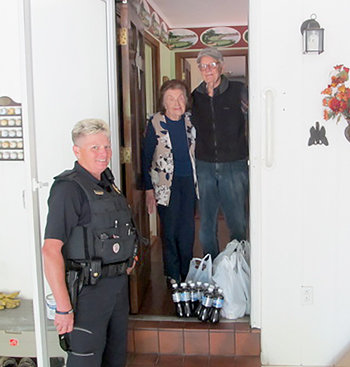Lt. Angie Barker delivers groceries to Mr. and Mrs. Pat Leathers, who reside on Northwood Drive in Huntingdon.