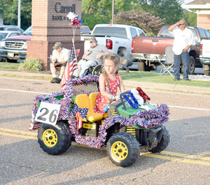 Addi Pugh rides a festively-decorated four-wheeler. Photos by Brad Sam/The Banner