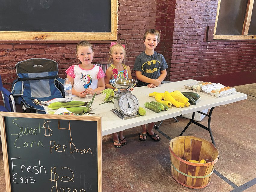 McKENZIE (July 18) — Caroline Perry of McKenzie, Alexis and Aiden Wheeler of Alabama were helping Matt Perry at his booth at the McKenzie Farmer's Market on Saturday. Area citizens sell vegetables, freshly brewed coffee, flowers, canned items, and homemade baskets at the market each Saturday morning. The city-owned facility is one of the only indoor markets in the area.