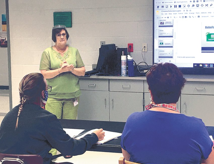 """McKenzie schools tech director Dianne Anderson, wearing a face shield, works with educators on the Aristotle K12 Program at a joint McKenzie/West Carroll """"Tech Day"""" of in-service training at West Carroll Jr./Sr. High School."""