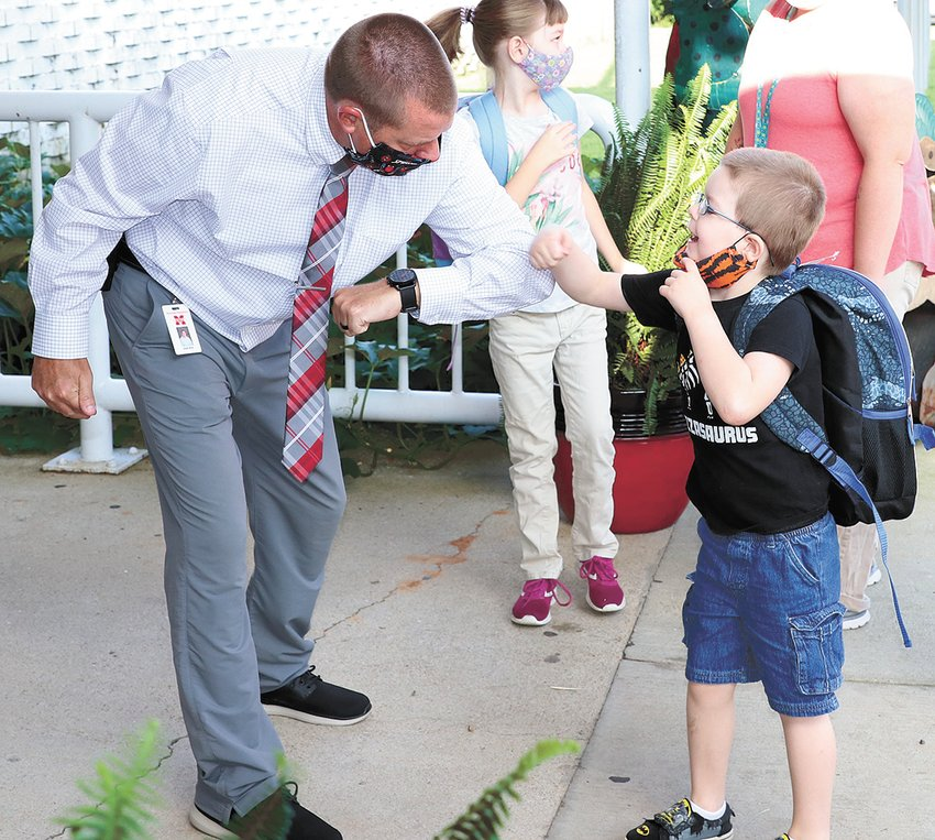 Ryan Davis gives McKenzie Elementary Assistant-Principal Josh Kee an elbow bump to start the school year.