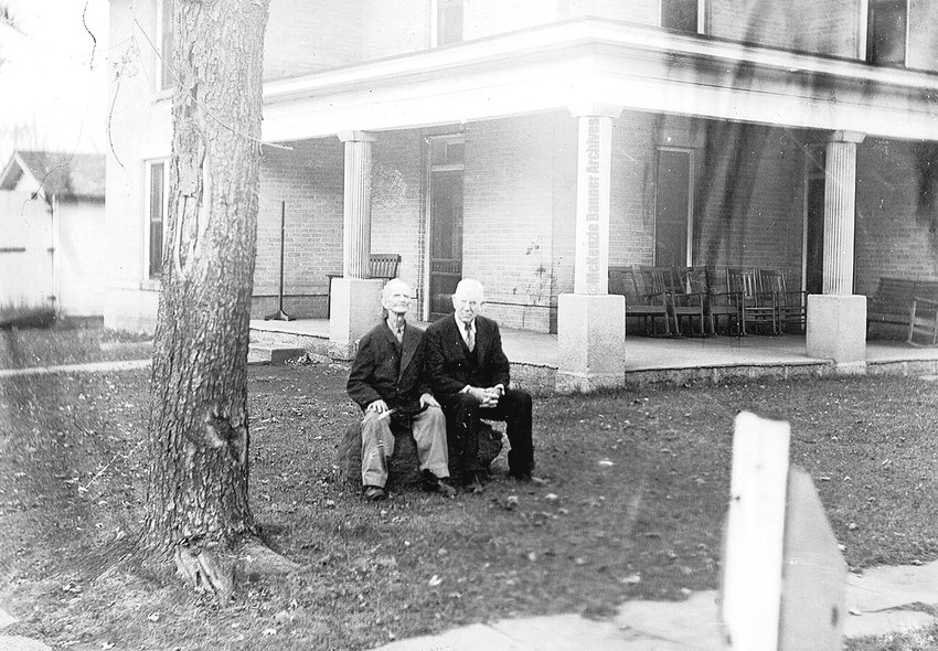 Dr. A. L. Dennison sitting on his rock (school house step) with his father-in-law, A. W. Wilson, in late 1920s, on Stonewall before it was paved.
