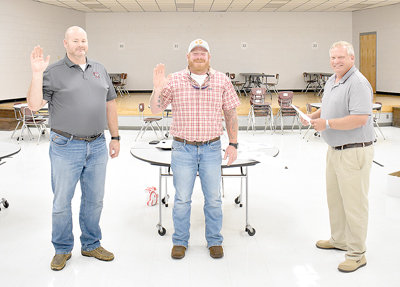 From left, newly-elected West Carroll school board members Jeremy Jackson and David Hilliard are sworn in by Chairman William Robinson.