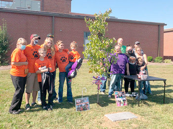 Family and loved ones of the late Carlie Hugueley gather at the tree dedication held at Gleason School.