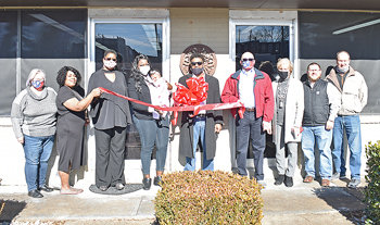 Weltonette Taylor cuts the ribbon at The Fellowship Hall. Pictured are (L to R): Jennifer Waldrup, McKenzie City Recorder; Amber Johnson, Amber's Boutique; Pamela Hannah, Pamela's Place; Weltonette (holding Jenesis Taylor); Jermaine Taylor; Councilman Bobby Young; Mayor Jill Holland; Daniel Hollowell, Maddox Insurance; and Joe Neumair, McKenzie Banking Company. Photo by Brad Sam/The Banner