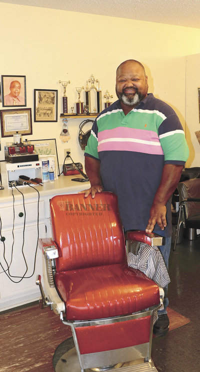Desmond Taylor at his barber's chair. A photo of the barbershop's namesake, Harold Howard, hangs on the wall at the workstation.