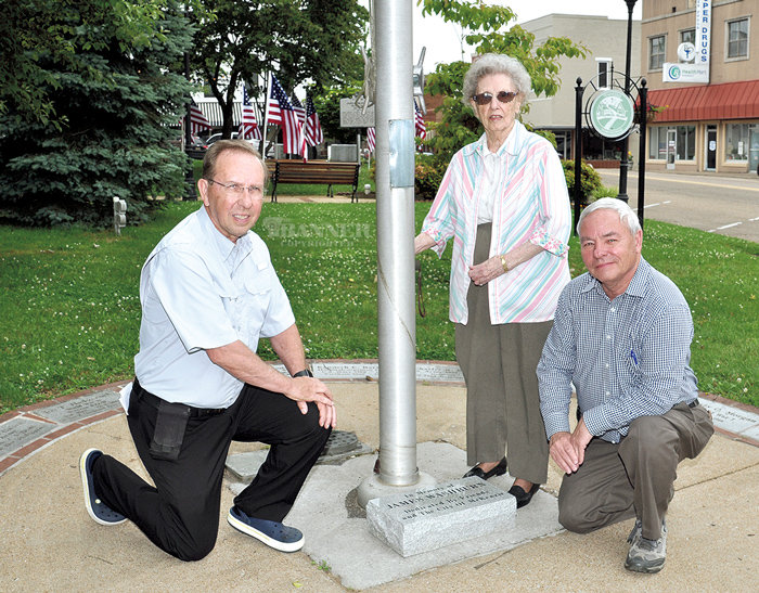 The flag pole at Veterans Park in Downtown McKenzie was rededicated to the late James L. Washburn on Friday. Pictured are his two sons Joel (left) and Jeff, and his widow, Ramona Washburn.