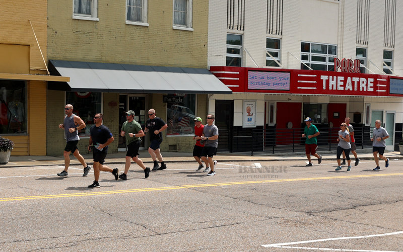 Henry County runners took refuge and refreshments following their run from Paris to McKenzie. Pictured are law enforcement and fire department personnel running down Cedar Street in McKenzie.