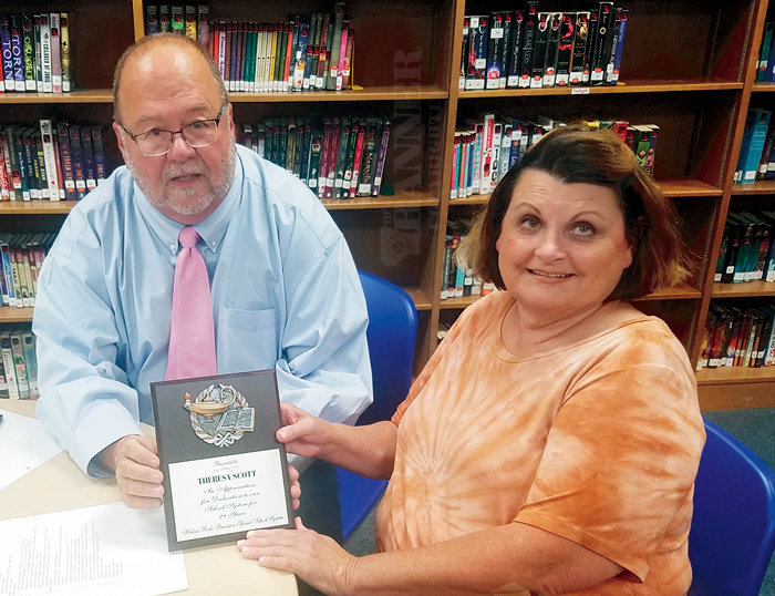 Brad Hurley, Chairman of Hollow Rock-Bruceton School Board presents a plaque to Theresa Scott upon her retirement.