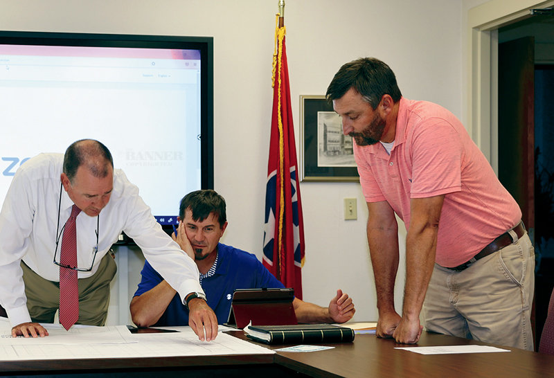 Lynn Watkins, school director, and school board members Jon Davis and George Cassidy look at the proposed multi-use sports practice complex proposed for the high school campus. No action was taken on the drawings during the meeting.