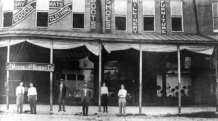 The Moore and Burns Company in downtown McKenzie. As indication on the store front, the store offered a variety of goods, including dry goods, hats, clothing, boots, shoes, millinery and furniture.