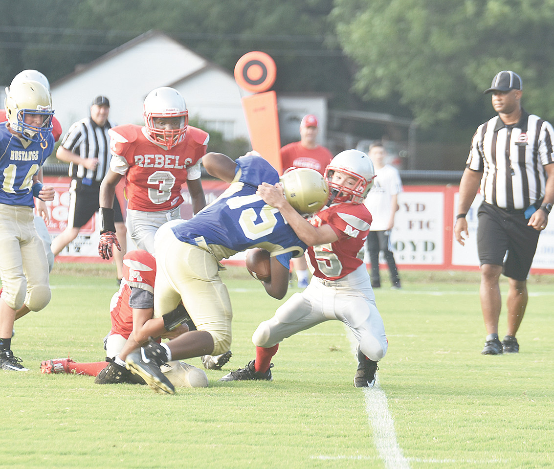 Mustang Tayshawn Rivers powers forward for a first down and is brought down by Rebel Zach Aird.