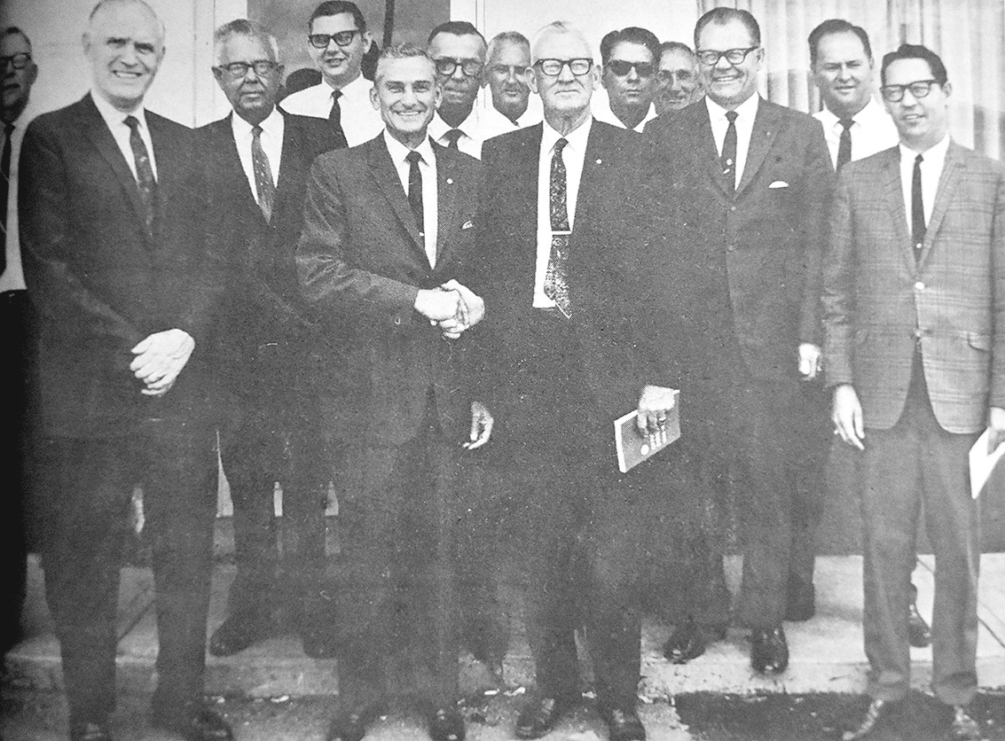 50 YEARS AGO — Amos Bailey Wrinkle, president of McKenzie Rotary Club, greets Leon Burnett, governor of Rotary District 6760, is surrounded by members of the McKenzie Rotary Club.