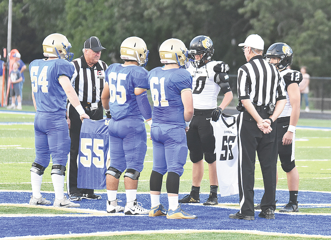 Mustang captains Matthew Ellis (54), Joseph Richardson (65) and Austin Avery (61) and Lion captains Jace Riley (10) and Heath Daniel (12) carry jerseys bearing the late Will Fisher's number 55 during the pregame coin toss.