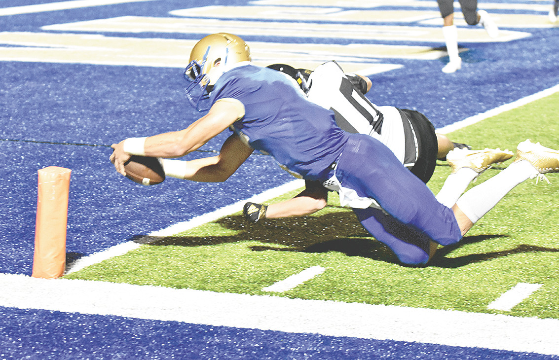 Mustang quarterback Hunter Ensley dives into the end zone for a ten-yard touchdown.