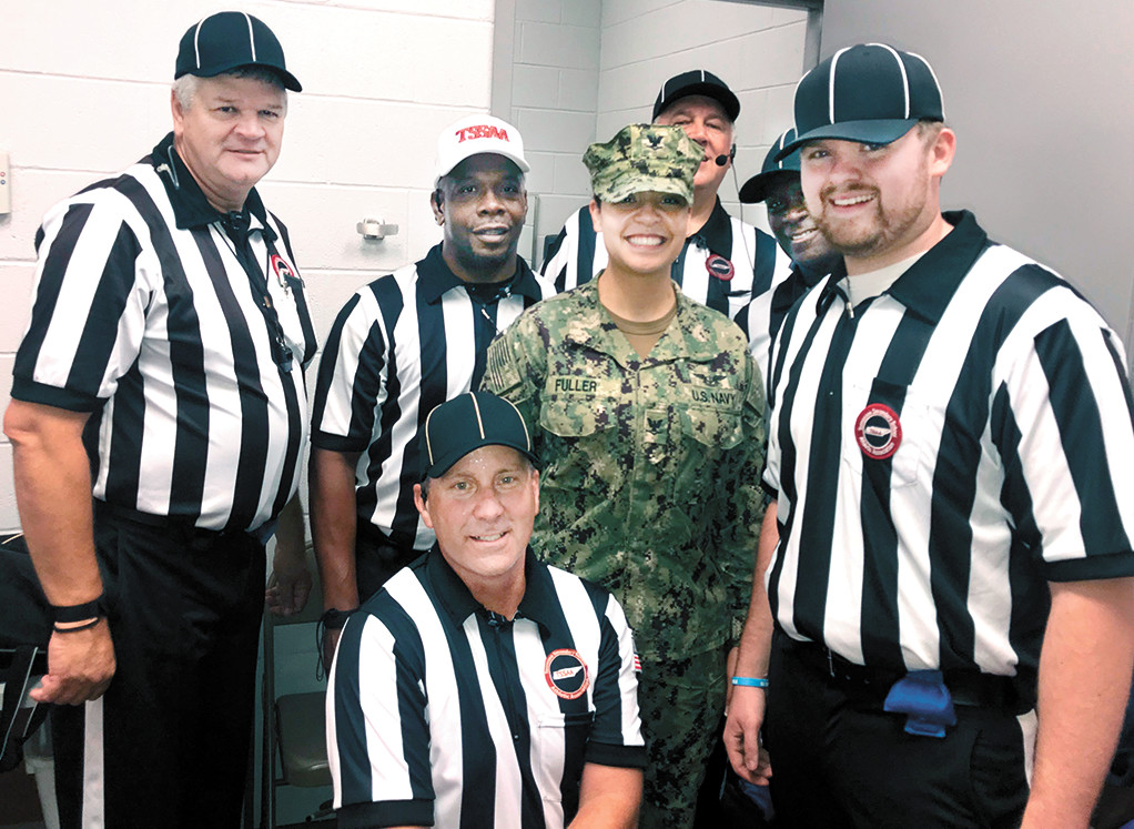 After halftime, the officiating crew asked Petty Officer Fuller to join them for photographs.