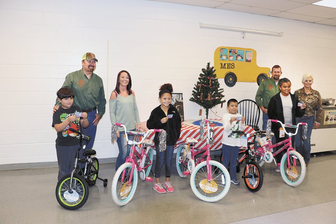 Anthony Landreth, Jerica Smith, Corey Reeves, and Tammy Trevathan distributed bicycles at McKenzie Elementary School. Five MES students received the free bicycles from the Brad Deming Memorial Bicycle Fund.