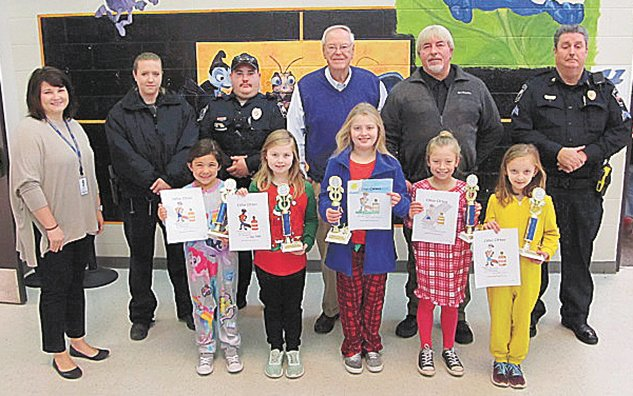 Pictured are (L to R) back row: Primary School Principal Christy Carey, School Resource Officer Jackie Allen, Officer Shelton Moon, Mayor Dale Kelley, Cmdr. Johnny Hill and Sgt. Rick Crossno.  Winners front row: Mia Villalobos, Hailey Foster, Harley Chandler, Marcie Mitecell and Joe Carter.