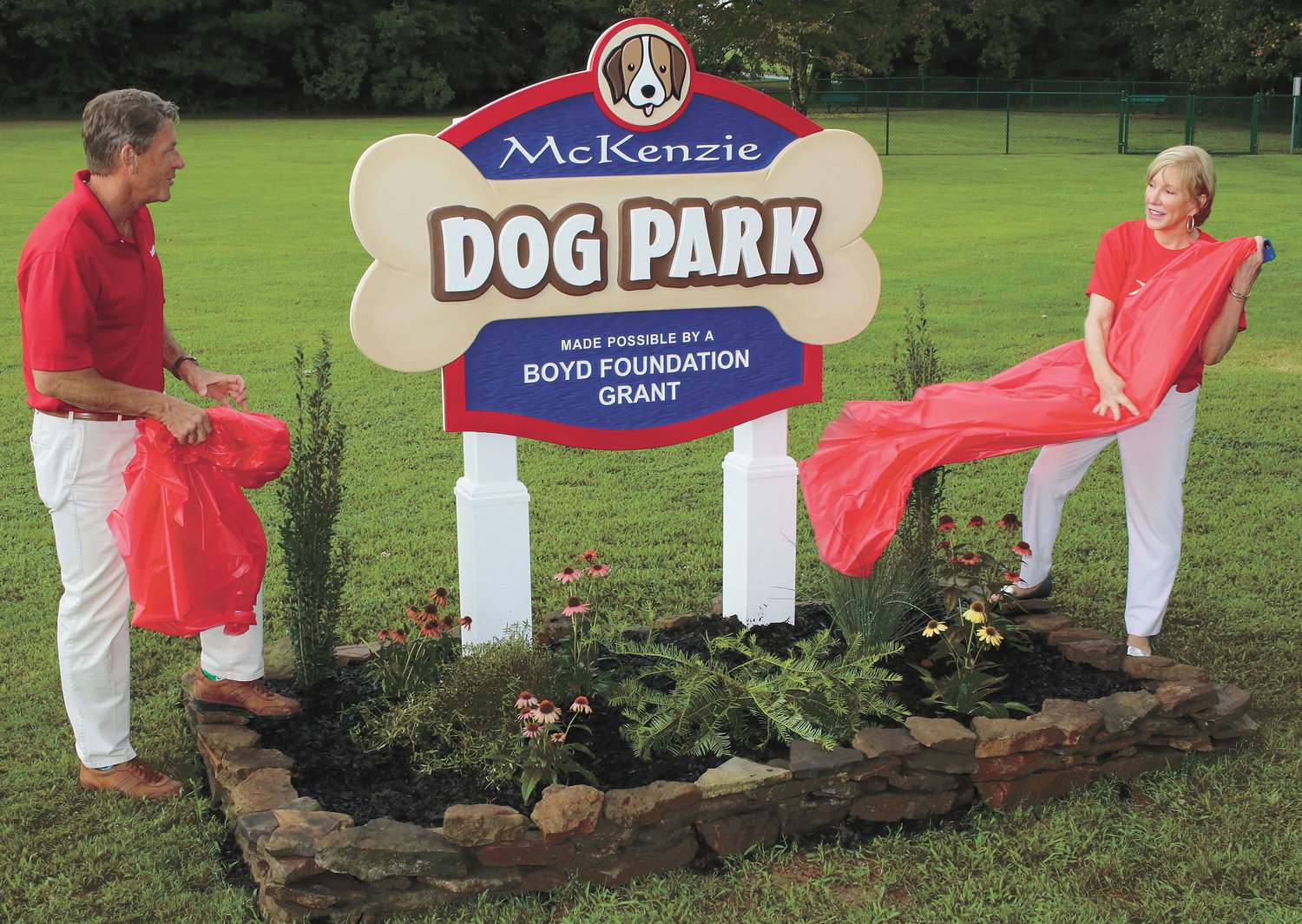 Randy Boyd and Mayor Jill Holland unveil the new sign, designed by Elliott's of McLemoresville. The dog park is free to use and is located adjacent to McKenzie City Park on Como Street in the year 2019.