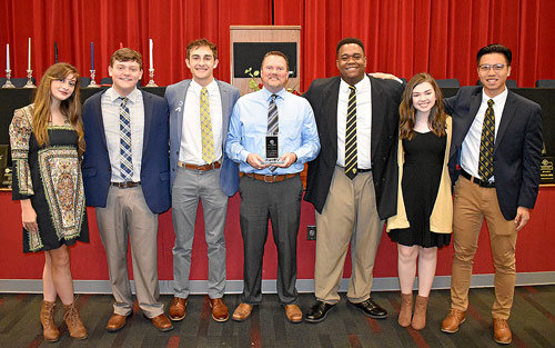 Former MHS teacher and Beta sponsor Kevin Gallimore was honored by the Beta officers during the ceremony for more than a decade of service to the club. Pictured are (L to R): Parliamentarian Isabella Colotta, Reporter Will Gallimore, Vice President Nathan Rorer, Kevin Gallimore, President Braxton Hobson, Secretary Lyndsey Summers and Treasurer Jackey Zheng.