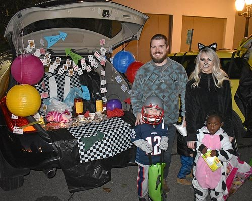 "Carroll County Mayor Joseph Butler, his wife, Megan, and their children, Harlon (left) and Joie, visit the trunk of Heather Dempsey (not pictured), elaborately decorated in the style of ""Alice in Wonderland."""