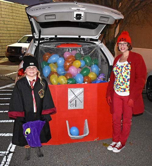"Anderson Pearson (left) in her Hogwarts uniform gets a treat from Patty Easley's ""gumball machine."""