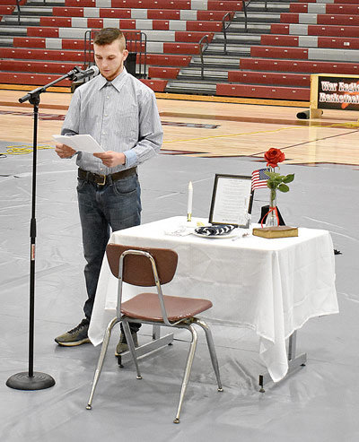 West Carroll student Tylor Freeman explains the symbolism of items at the Fallen Soldier Table.