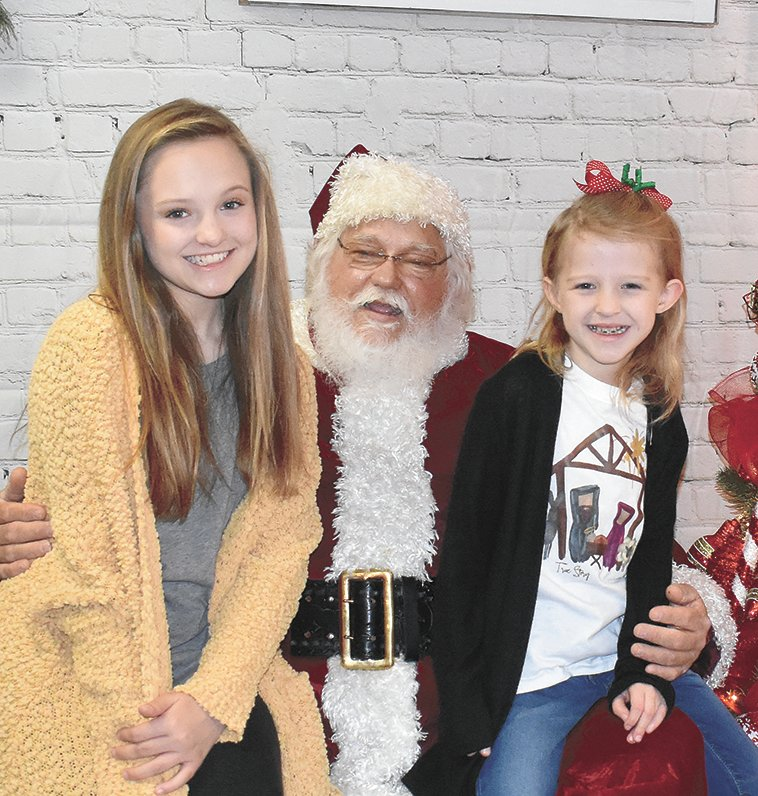 Sisters Brett Toombs, 13, and Marlee Toombs, 8, tell St. Nick what they want the most at Beta Sigma Phi's Breakfast with Santa.