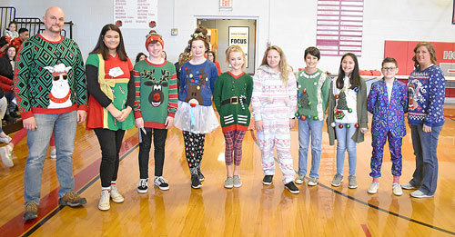 Ugly sweater contest winners (L to R): teacher Mike Pershell, eighth graders Madison Thomas and Brady Brewer, seventh graders Olivia Steen and Emmy McMullin, sixth graders Haylee Beard and Aiden Mason, fifth graders Emma Haynes and Ripken Thompson and teacher Bess Toombs.