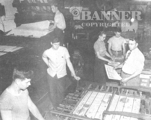 In the pressroom, during the early fifties, Frank Barlow looks over a copy of the newspaper as it comes off the folding machine. Immediately to the left is son, Karl Barlow, future owner. Hand-feeding the press in the top upper left is future owner James Washburn.