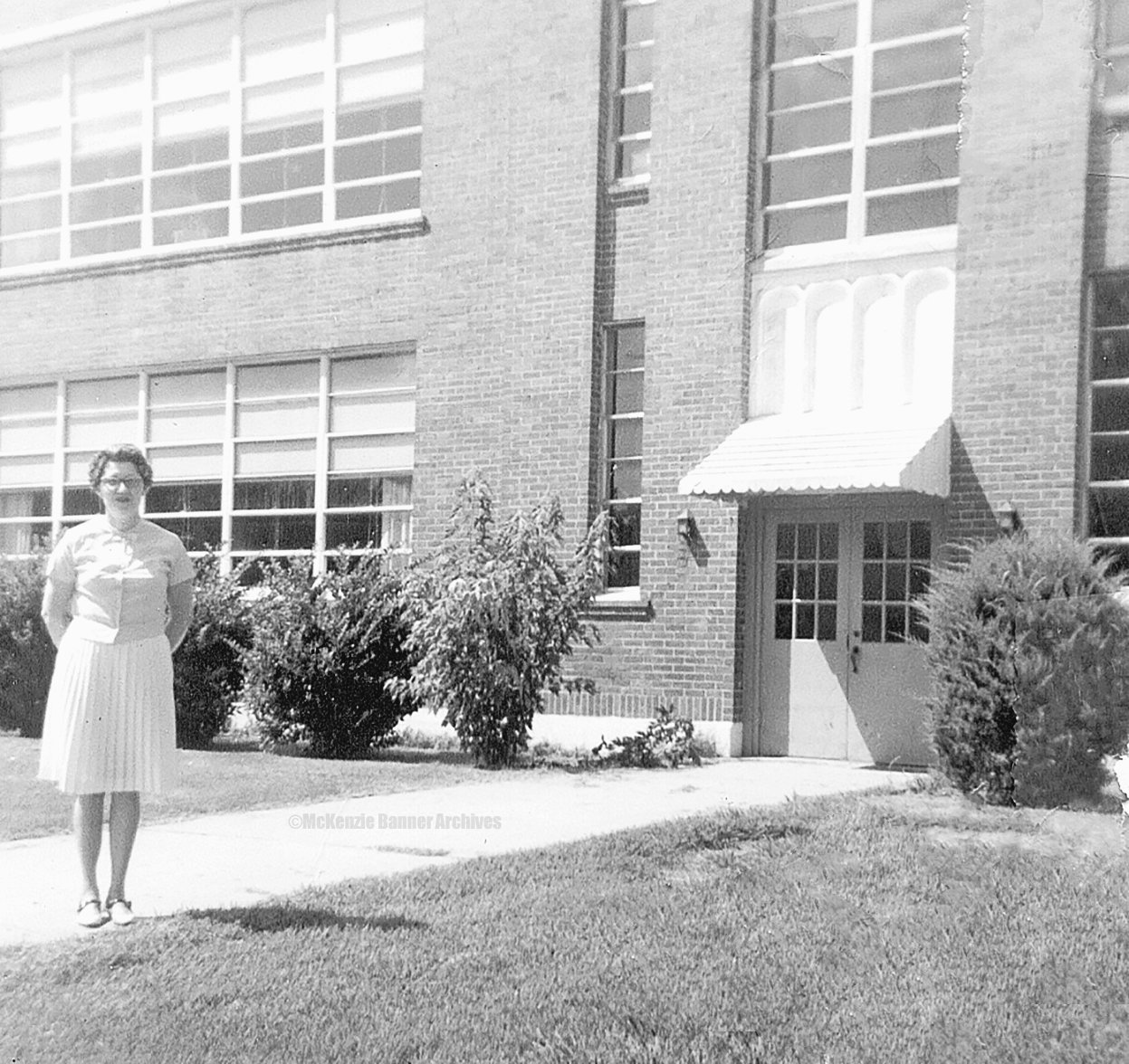 McKenzie Elementary Teacher, Ruth Brashear, stands in front of the old Elementary School on Woodrow Ave., 1967.