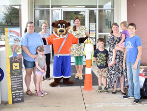 Ollie Otter visited the Carroll County Library Thursday. Pictured are (L to R): Alicia and Zoe Suddath of Cedar Grove; children's librarian Grace Hawkins; Ollie Otter and West Tennessee Coordinator Jennifer Tyler; and Will, Rose and Delilah Arnold and Cole Petty, all of Holladay.