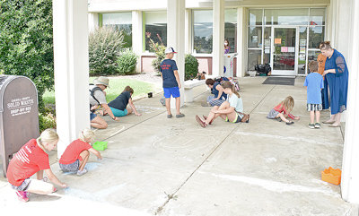 Summer readers cover the walk in front of the Carroll County Library with colorful chalk art.