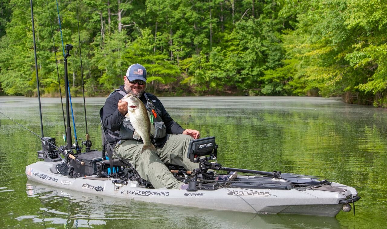 Chad Hoover, president of the Kayak Bass Fishing organization, catches a large mouth bass from his kayak.