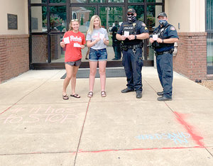 McKenzie High School students Ashlyn Drewry (left) and Maggie Glass pour red sand outside McKenzie City Hall with McKenzie Police Officers.