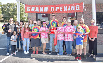 Owners Lisa Weaver and Chris Singleton (center) cut the ribbon at McKenzie Nutrition's Grand Opening Saturday.