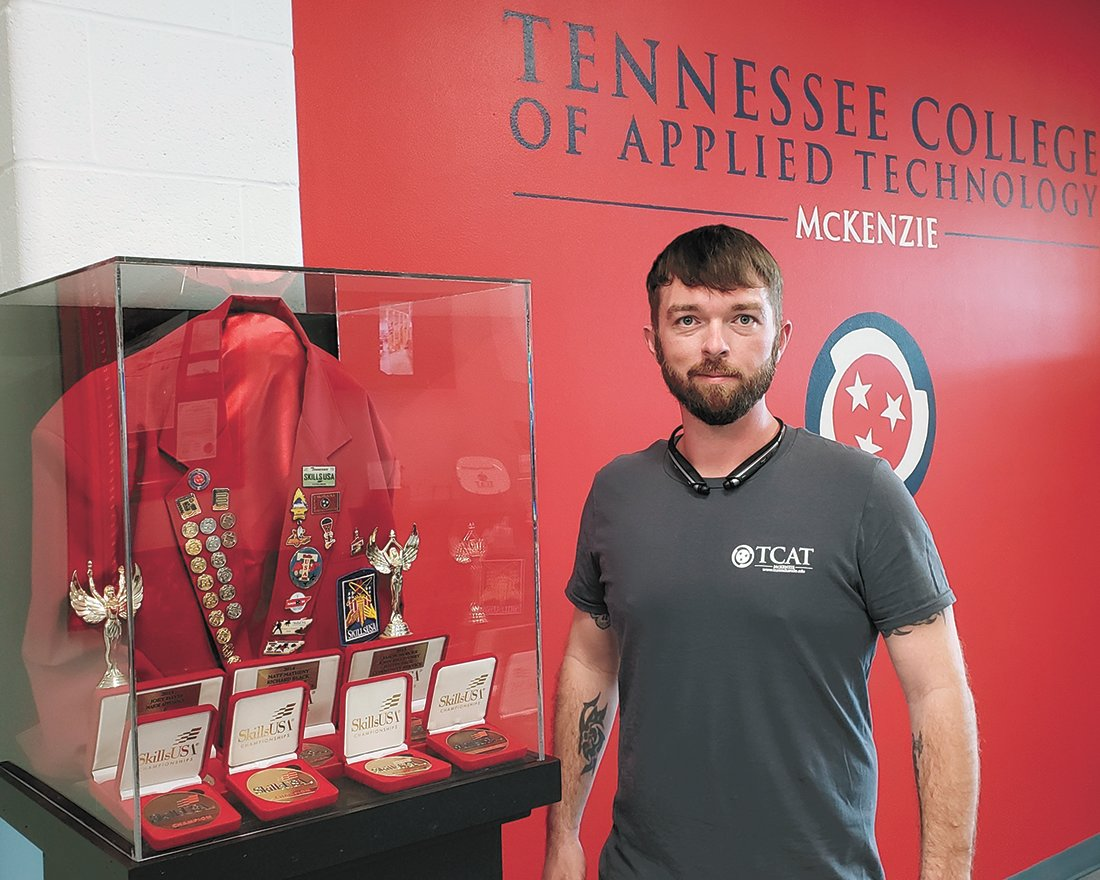 Dustin is pictured with the display of former instructor Terry Wilson's SkillsUSA Jacket and advisor medals won throughout his career as an instructor.