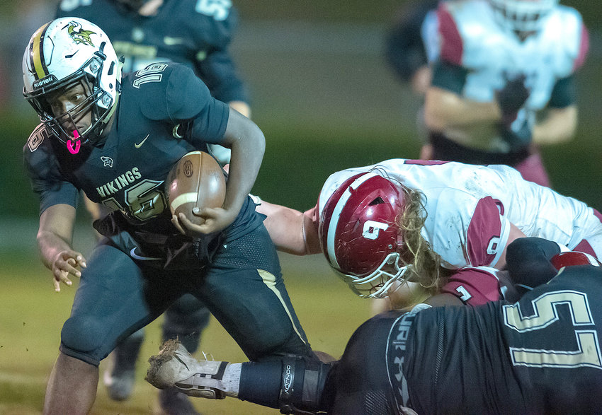 Jasper's Cam Lambert tries to escape the grasp of a Deshler defender during Friday night's game at Ki-Ro Gambrell Field. The Vikings won 36-27.