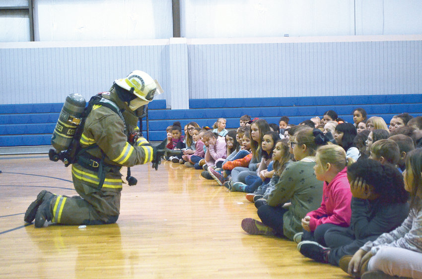Colt Courington of Oakman Volunteer Fire and Rescue teaches students not to be afraid of a firefighter's uniform. Oakman Volunteer Fire and Rescue visited Oakman Middle School Friday to teach students about fire safety and emergency medical services. Regional Air Medical Services and Regional Paramedical Services assisted.