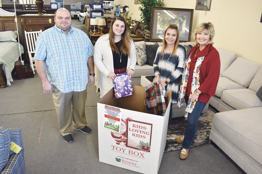 Kids Loving Kids is collecting clothes and toys at 65 local sites, including Barry's Furniture. Gathered at that collection site Wednesday were, from left, the store's manager, Dan Stallter; sales representatives Samantha Stallter and Kara Miller; and Pam Dodd, founder of Kids Loving Kids.