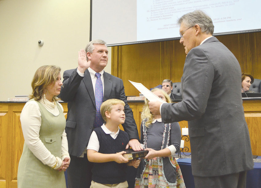 Dr. Joel Hagood, joined by his wife, Jennifer, and children, Breck and Annleigh, is sworn in Thursday as superintendent of education for the Walker County Schools. Circuit Judge Hoyt Elliott administered the oath of office.