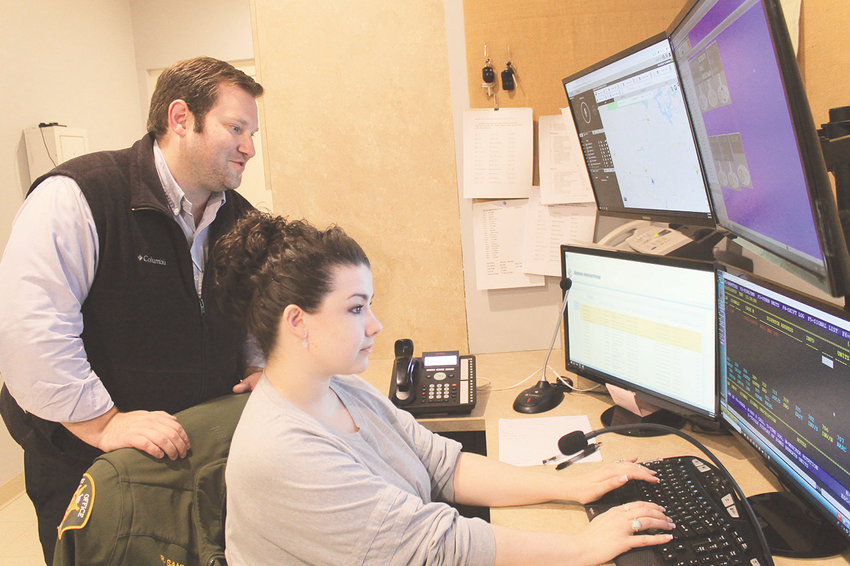 Nick Key, director of operations at Walker County Sheriff's Office, chats with dispatcher Rachel Sanders while she works on Thursday.