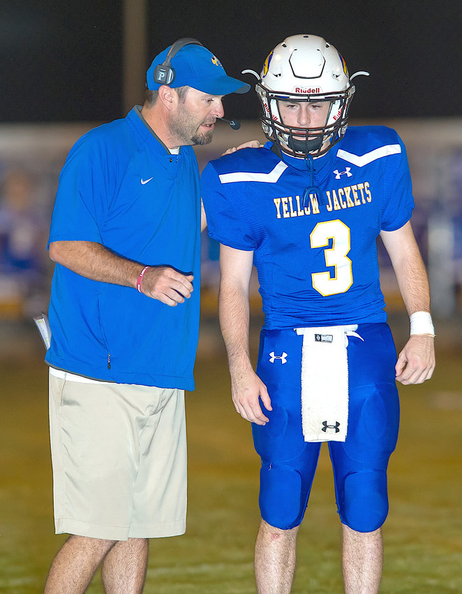 Curry football coach Philip Smith talks to his son Luke Smith during a game against Haleyville last season. Smith stepped down from his post as head coach last week.
