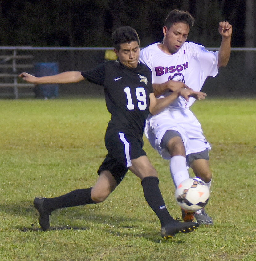 Jasper's Oscar Hernandez (19) battles a Parker High School player for the ball during their area game at the Jasper toy bowl field on Monday. Jasper won the game 4-1 to win the area title.