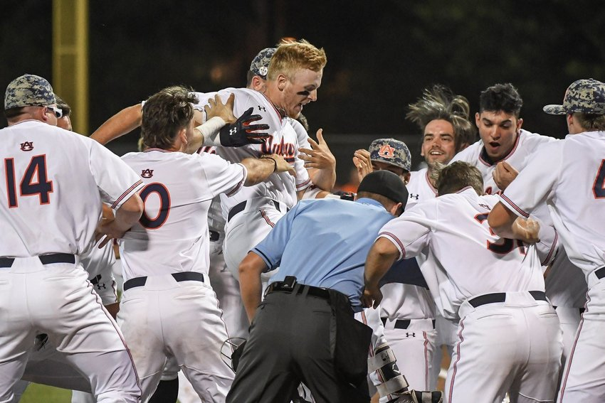 Auburn's Steven Williams is mobbed by teammates at home plate following his walk-off, three-run home runs against Georgia Tech on Saturday.