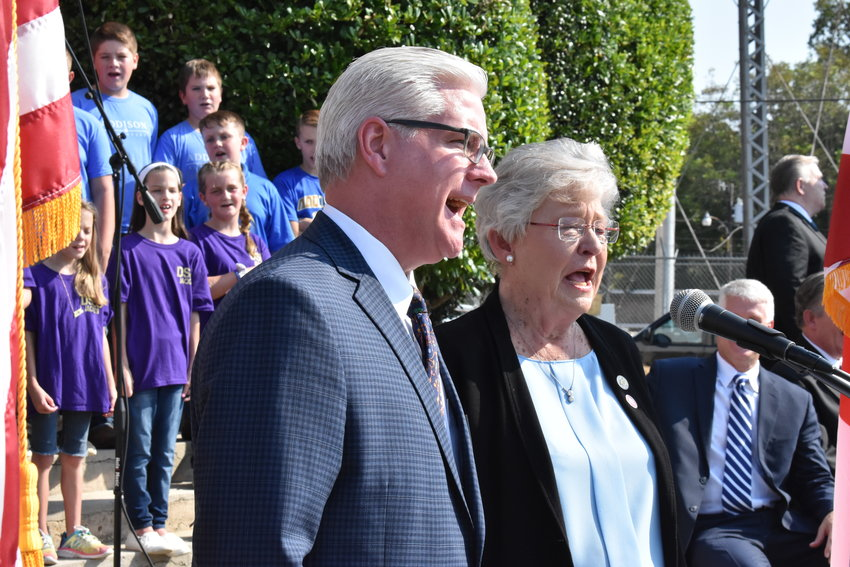 """Gov. Kay Ivey and Senate Majority Leader Greg Reed, R-Jasper, sing """"Happy Birthday"""" to the state of Alabama at the end of a celebration of the state's bicentennial at an outdoor ceremony Wednesday at the Winston County Courthouse in Double Springs. The ceremony also saluted Winston County schools honored in the state's bicentennial school program, and heavily involved local students that morning."""