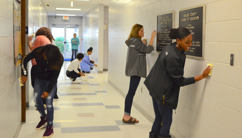 Students clean some walls at Oakman High School on Friday as part of a service day.