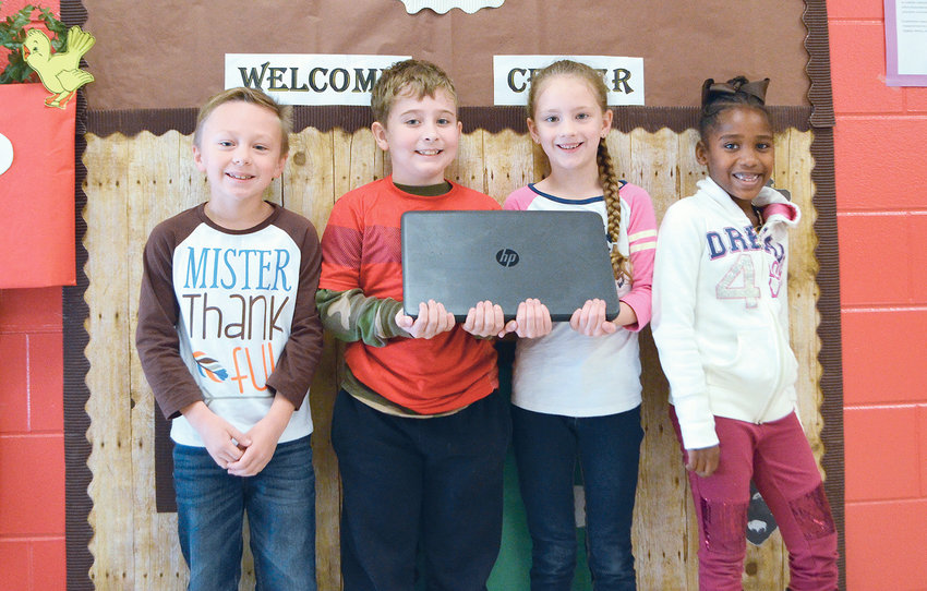 Students at Parrish Elementary School pose with one of seven laptops that were donated to the school from Charter Communications.