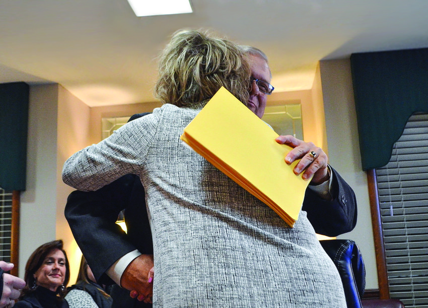 The Jasper City Board of Education recently recognized 80 years of the 'Black Gold' yearbook. Pictured, sponsor Mike Cordle hugs Superintendent Dr. Ann Jackson.